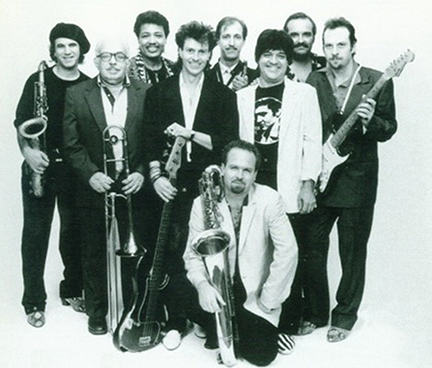 Roomful of Blues 1987. One of the many lineups of the band during the transitionary years between record deals. Back row, left to right: Greg Piccolo, Junior Brantley, Rich Lataille, Bob Enos, Ronnie Earl. Front row, left to right: Porky Cohen, Paul Tomasello, John Rossi. Kneeling in front: Doug James.